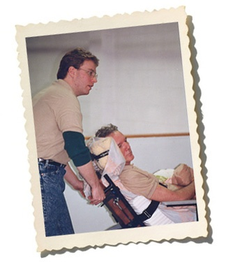 Brian Radwell carring his father in a wheelchair